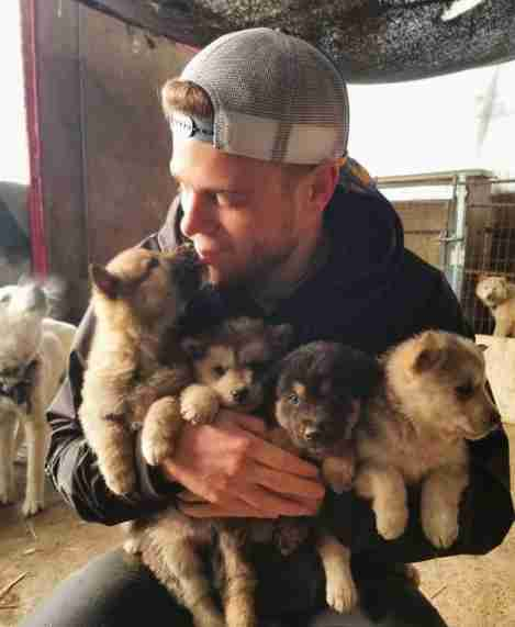 Olympic skier holding rescued puppies