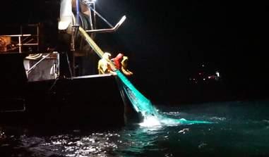 Fishermen pulling net onto a boat