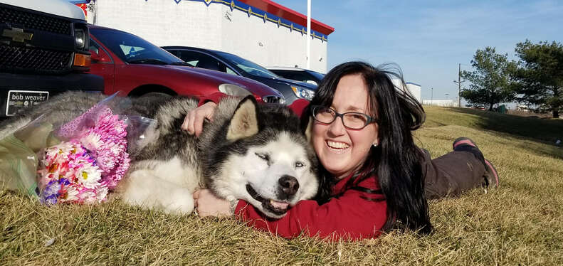 Woman posing with husky on the ground