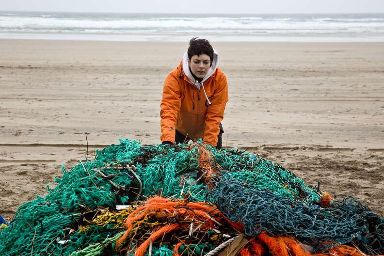 Woman handling a ghost net on a beach