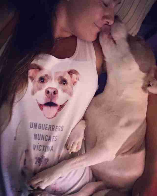 Woman cuddling with smiling dog