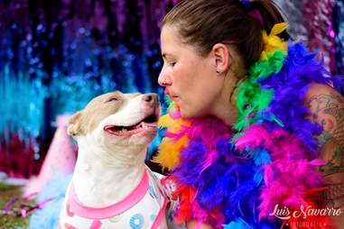 Dressed-up woman posing with smiling puppy