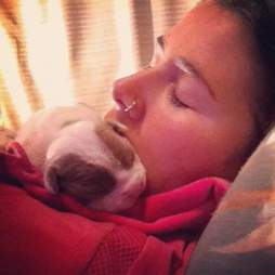 Woman cuddling with newborn puppy