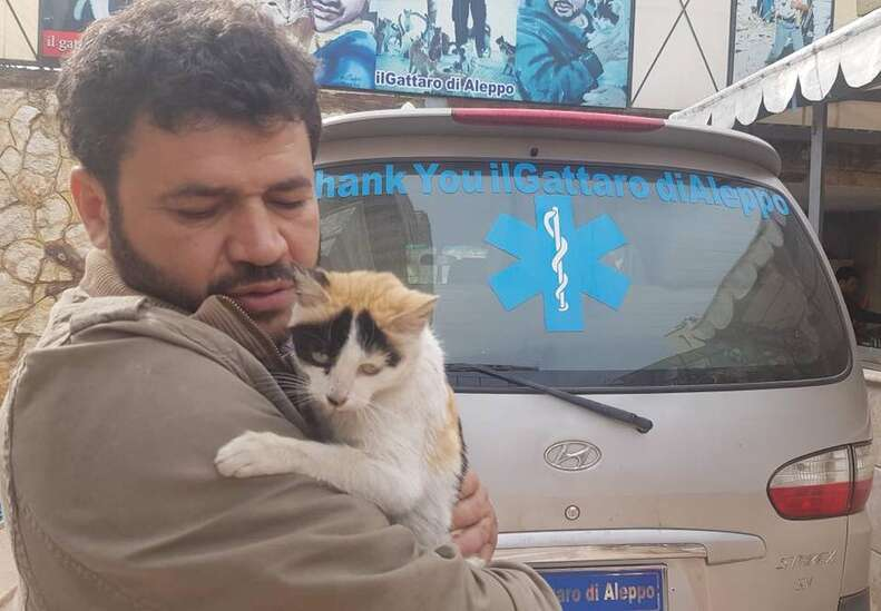 Man holding cat in front of ambulance