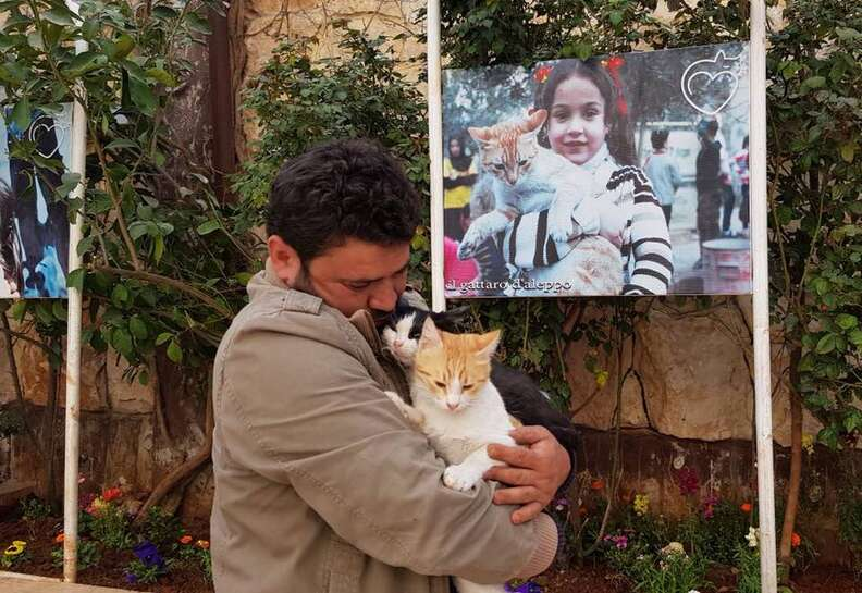 Man holding cats in courtyard