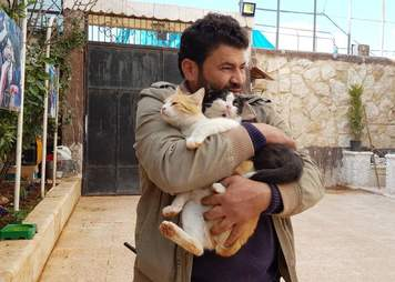Syrian Man hugging cats to him