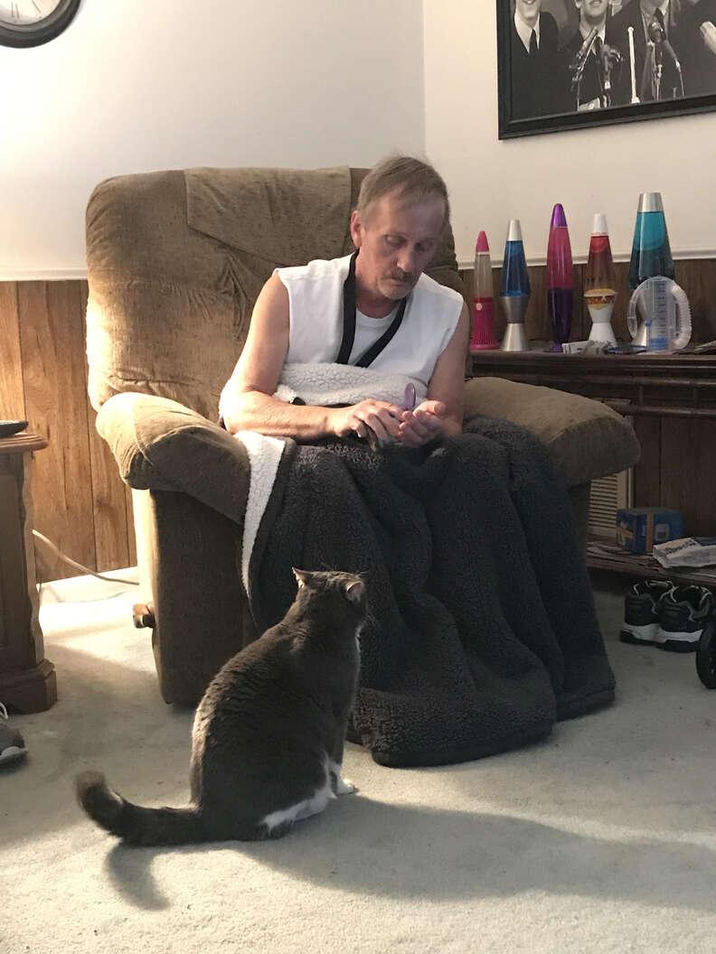 Man feeing cat treats