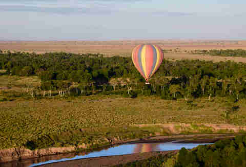 A hot air balloon soars above the African plains