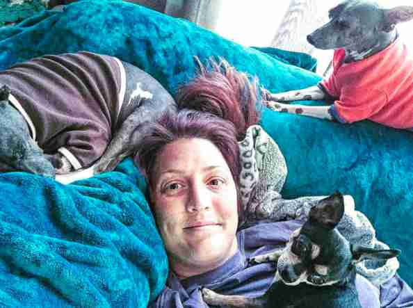 Woman lying on couch with special needs dogs