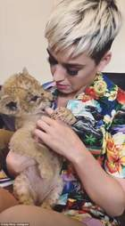Singer Katy Perry cuddling a baby lion