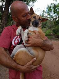 Man holding rescued dog in his arms