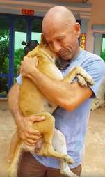 Man holding a dog her just rescued