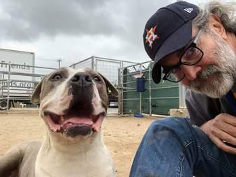 Man sitting next to smiling dog