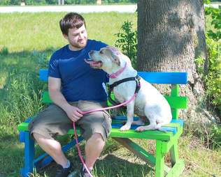 Dog sitting on bench with man