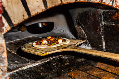 pizza going into the oven, brick oven