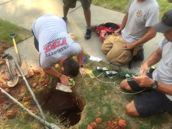 Charlotte fire fighters measure the hole that the puppy fell down