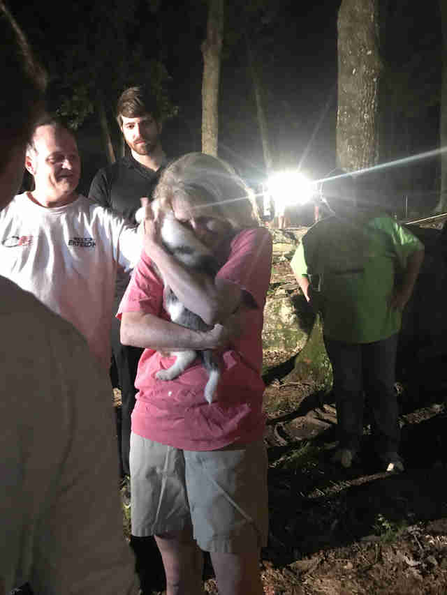 Woman holding puppy after she was rescued
