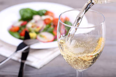 white wine poured into glass paired with salad