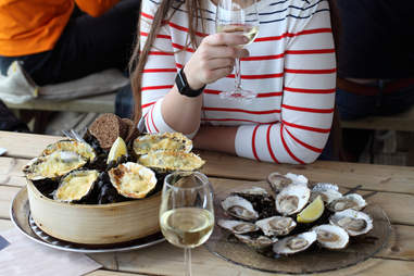 Woman eating oysters and drinking white wine outdoors