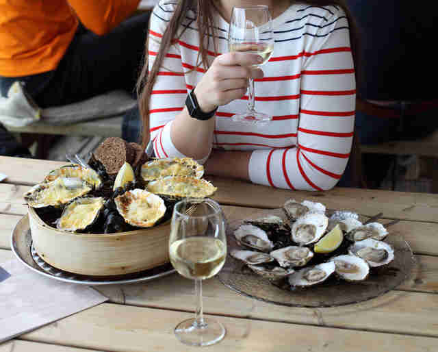 Woman eating oysters and drinking white wine
