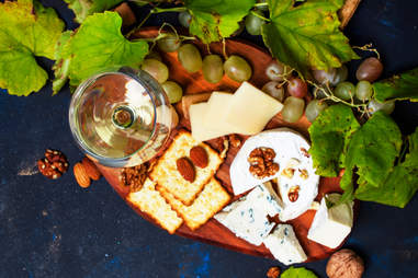 white wine, blue cheese, crackers, nuts, and grapes on a platter