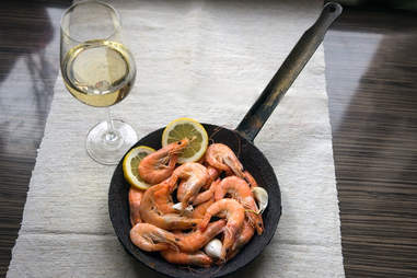 shrimp and lemons in a skillet and glass of white wine
