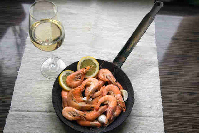 shrimp in a skillet and glass of white wine