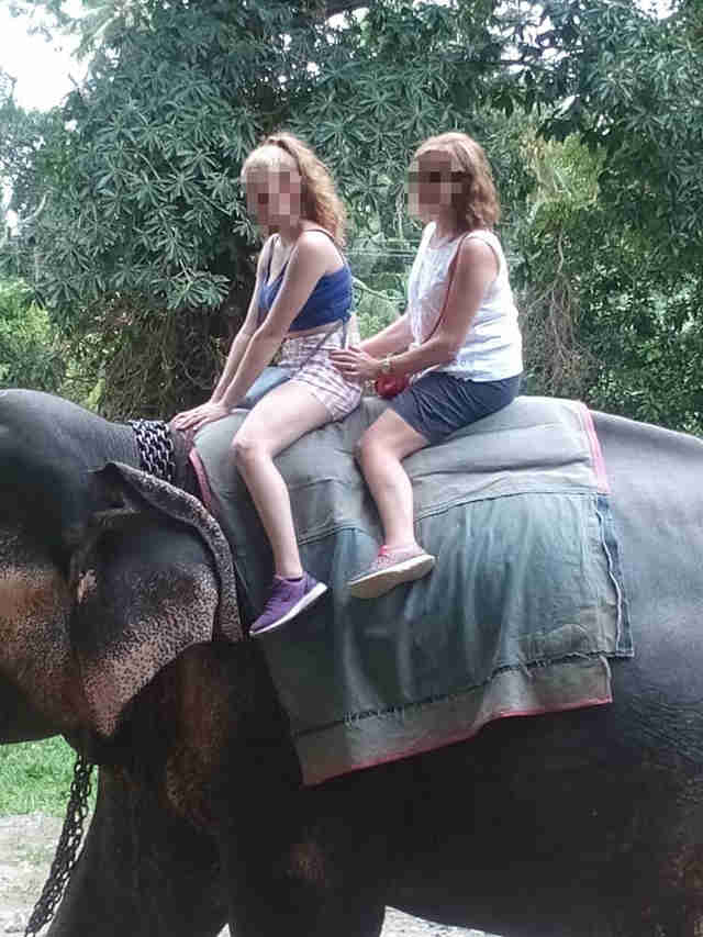 Two women riding on the back of an elephant