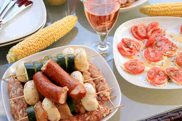 sausage, corn on the cobb, and rosé