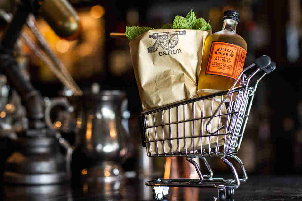 Canon Seattle cocktail bar bourbon bottle in mini grocery cart