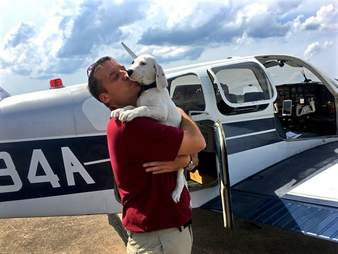 Paul Steklenski poses with a rescue dog and his plane