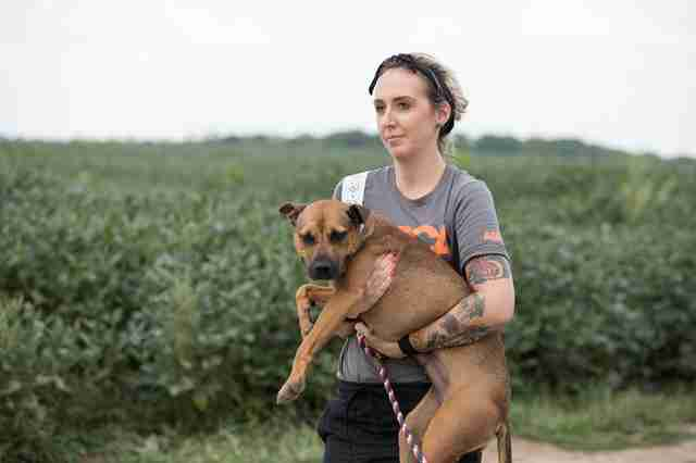 Woman carrying rescued dog in her arms