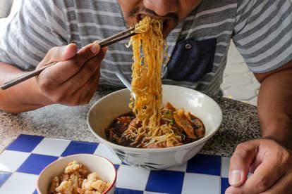 man slurping noodles