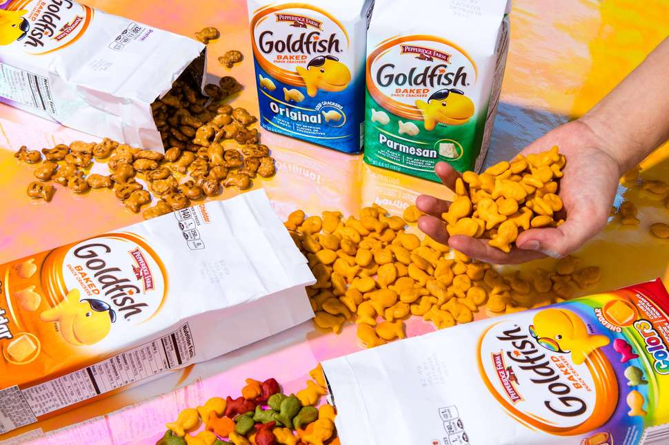 different flavors of goldfish in hands and spread on table