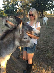 Rescued donkey gets a hug from rescuer