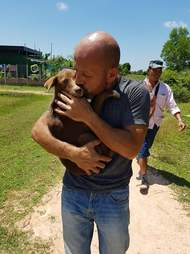 Man cradling rescued dog in his arms