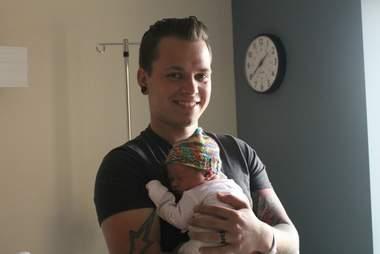 Korey Taphouse holds his newborn daughter