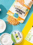 vegan cheeses scattered: Kite Hill ricotta and chive cream cheese tubs, Daiya mozzarella slices and shreds, orange Follow Your Heart cheddar shreds, and Treeline soft cheese