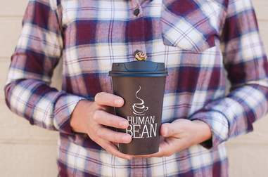The Human Bean paper coffee cup held