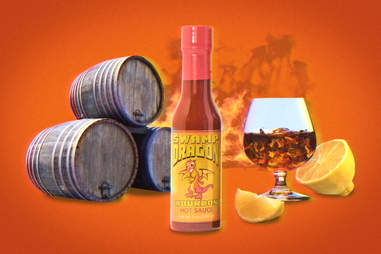 Swamp Dragon bourbon hot sauce depiction with barrels, a glass, a lemon, and fire in background