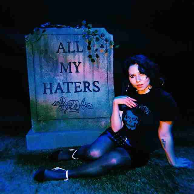 "Girl next to gravestone that says ""All My Haters"""