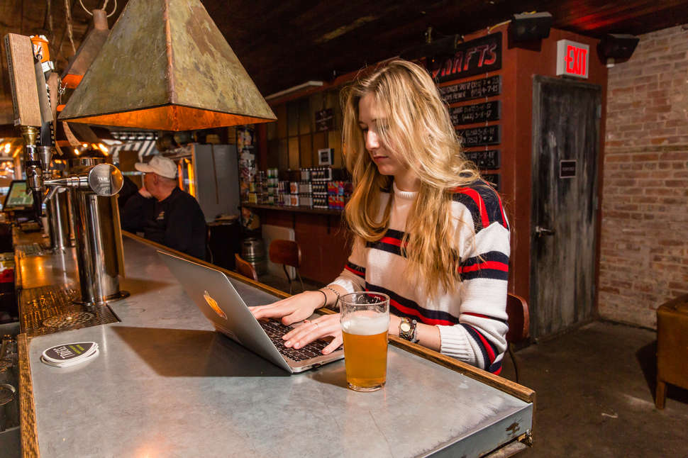 woman working in bar on laptop