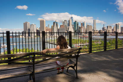 woman sitting on bench on Brooklyn Promenade in front of skyline