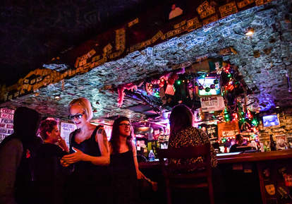 woman checking her phone in a dive bar
