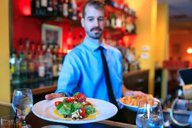 waiter serving pasta
