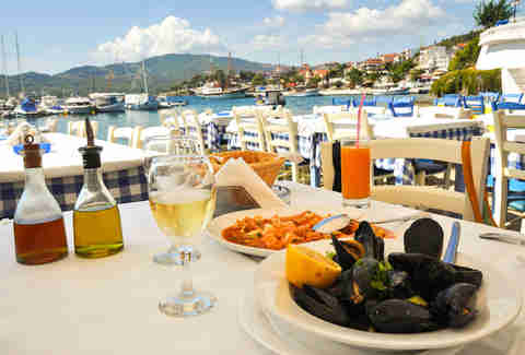 Seafood dinner in a Greece restaurant, Mediterranean sea resort with white wine