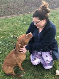 Woman with pit bull out in grassy yard