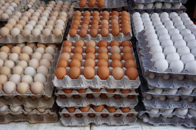 cardboard crates of fresh white, yellow and brown eggs