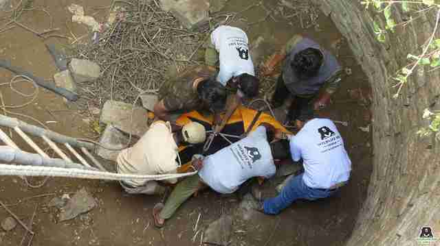 Rescuers helping injured sloth bear