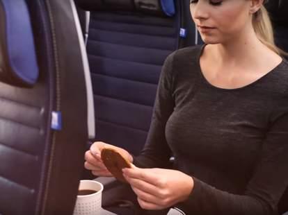 woman eating stroopwafel on plane